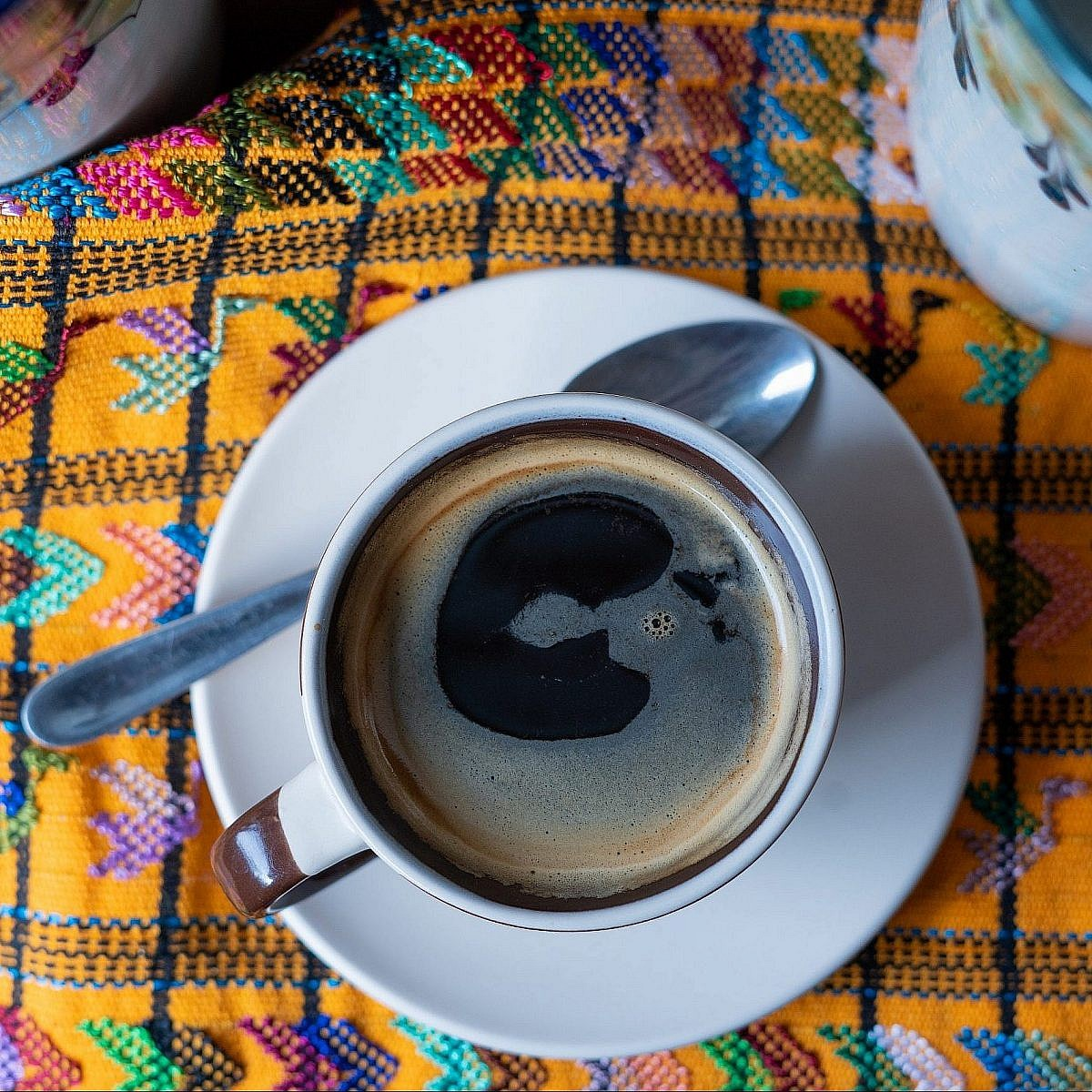 Photo of coffee in cup on brocaded tablecloth taken in Guatamala